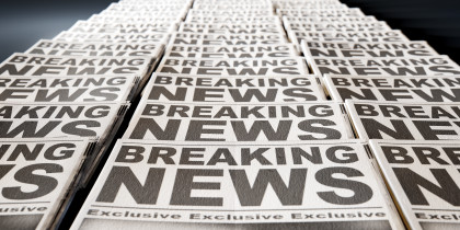 A long row of folded newspapers at the end of a press run with a generic headline that reads breaking news on the front page on an isolated white background; Shutterstock ID 248829895; name: Deb; Client: TCS; Publication: TCS; Story ID: Optimize Headlines